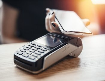 Young woman pays via payment terminal and mobile phone in cafe.